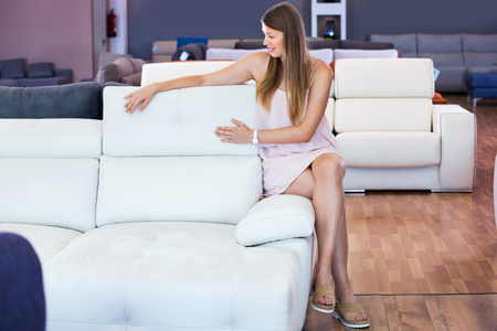 Adult happy positive smiling female touching sofa in the furniture store before the buying Stock Photo