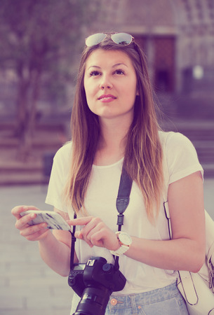 Female-tourist is looking up the way in phone by using gps.