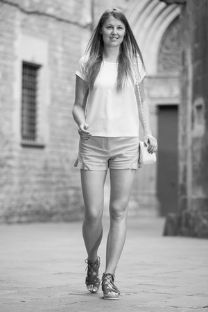 Stylish young woman strolling past old stone castle in summer day Stock Photo