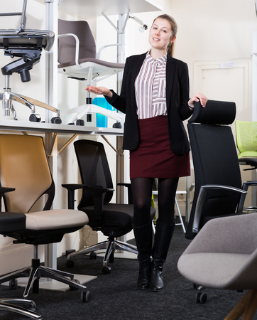 Full-length portrait of polite salesgirl inviting to furniture salon with wide selection of chairs