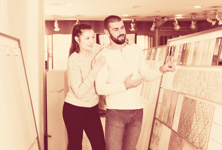 Young couple choosing kitchen ceramic tile in modern store