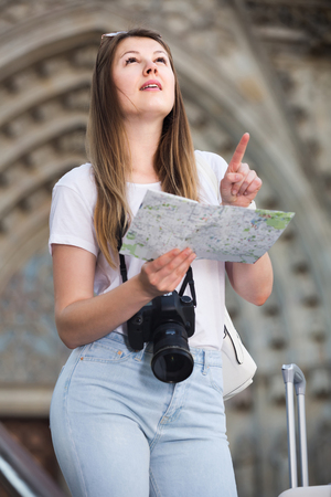 young happy woman having  map and looking for her route in the city Stock Photo