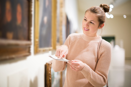 Portrait of young pensive female visitor with guide book looking at exposition in museum