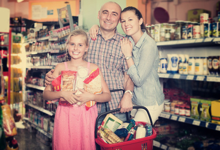 Happy family with girl in the supermarket choosing food Stock Photo