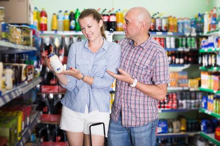 Woman and man choosing mayonnaise at the modern supermarket Stock Photo