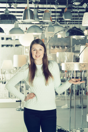 Young female  standing near modern lamp  in the  designer furniture store