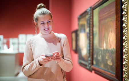 Positive woman visitor using  phone  in the historical museum