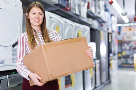 Portrait of cheerful young woman with box in household appliances shop Stock Photo
