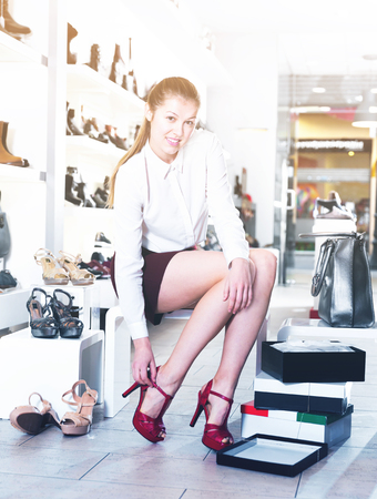 Cheerful smiling woman is trying modern summer shoes in a shoes store Stock Photo