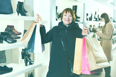 Adult female is showing bags with purchases in the store