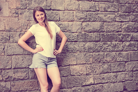 Portrait of romantic attractive girl on old town street with stone wall background Stock Photo