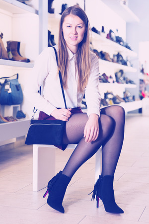 Young woman is posing with new handbag and fashion footwear in boutique.