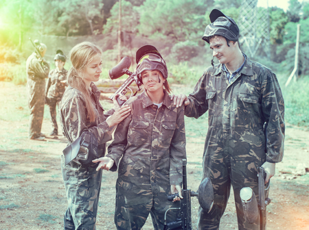 Paintball team calming upset girl after the losing match on open playing field Stock Photo