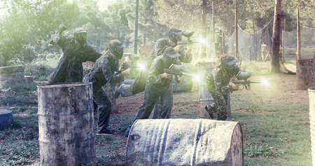 Dynamic paintball battle. Group of people in full paintball equipment attacking opposite team Stok Fotoğraf