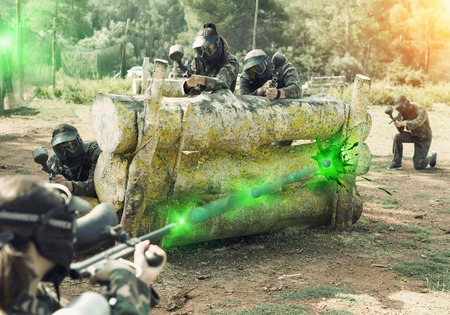 Portrait of  opposing teams in  camouflage playing  paintball  against each other outdoors Stock Photo