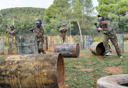 Paintball players aiming and shooting with marker guns at an opposing team outdoors Imagens