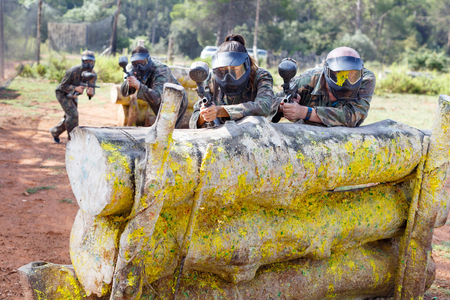 Portrait of team of positive smiling adult people playing on paintball battlefield outdoor Фото со стока - 111331063