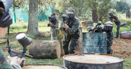 Two active opposing teams with guns playing paintball against each other  outdoors in forest