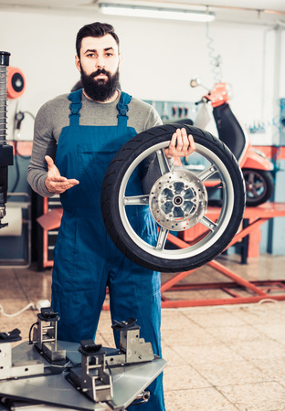 Work motorcycle repair shows the repaired tire on a scooter Stock Photo