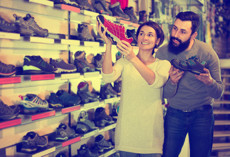 Happy couple examining various sneakers in sports equipment shop