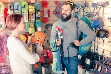 Beautiful couple deciding on climbing equipment in sports equipment store