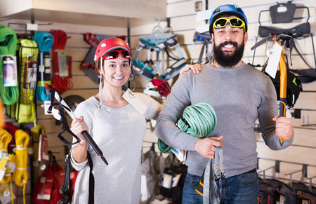 Young couple choosing alpinism equipment in sports equipment store