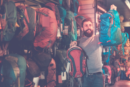 Positive guy deciding on new rucksack in sports equipment store