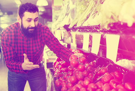 Glad male seller offering tomatoes in grocery shop Stockfoto