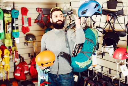 Smiling guy deciding on new helmet in sports equipment store