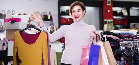 Young woman is showing her purchases in women's cloths shop.