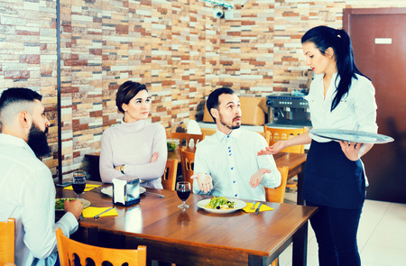 Unpleased angry client talking with manager in restaurant