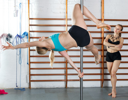 Attractive sporty girl pole dancer exercising dance moves at gym