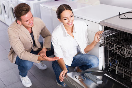 Young family selecting modern dishwasher in hypermarket and smiling Imagens