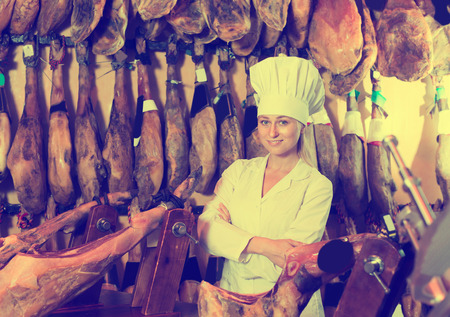 Happy female selling delicious prosciutto meat on market