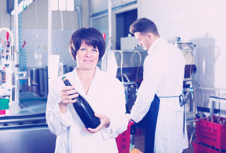 Positive senior woman worker displaying wine bottle at sparkling wine factory Stock Photo - 111326682