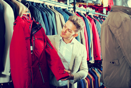 Ordinary male customer examining coats in men's cloths store Imagens