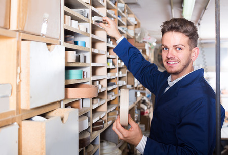 Young smiling american guy choosing strips to end edgings at workshop