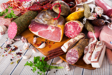 Variety of meats, sausages and mince with herbs on table Stock Photo