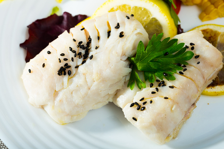 Dietary merluccid hake fillets steamed, served with lemon and greens