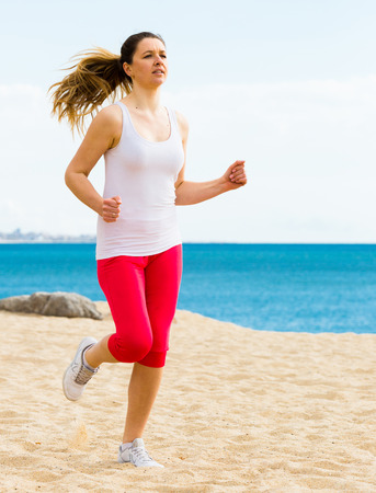 Smiling young girl running on beach by sea at daytime Imagens