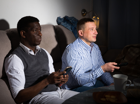 Two male interracial friends  watching football game at home together