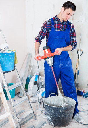Positive young worker mixing dry mortar with handheld mixer in bucket