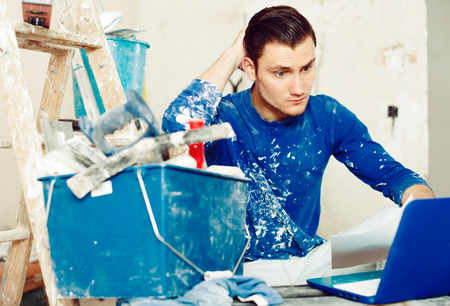 Young male contractor renovating house, working with papers and laptop in repairable apartment Stock Photo