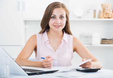 Smiling girl sitting at table at home calculating domestic finances and bills Imagens