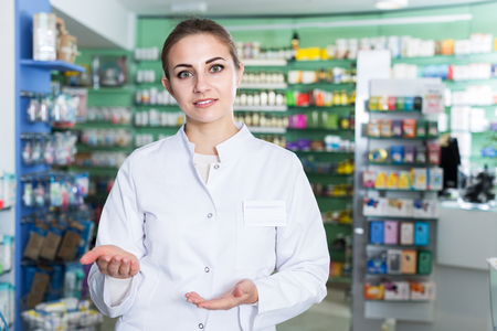 Portrait of positive woman specialist who is standing near shelves in pharmacy