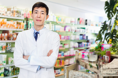 Portrait of chinese cheerful positive man pharmacist who is standing on his work place in apothecary.
