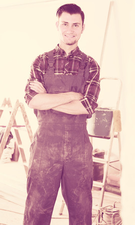 Portrait of young smiling builder standing in repairable room Stock Photo