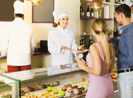 Smiling cheerful positive female pastry chef helping customers to choose pasrties in comfortable cafe