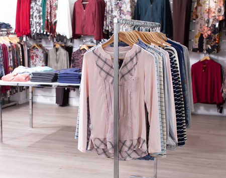 View of clothing boutique hall with colorful clothes on hangers and shelfs Stok Fotoğraf