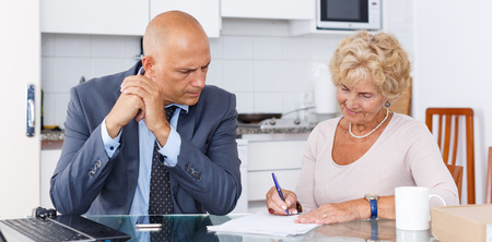 Sales agent helping to elderly woman fill out purchase order in kitchen